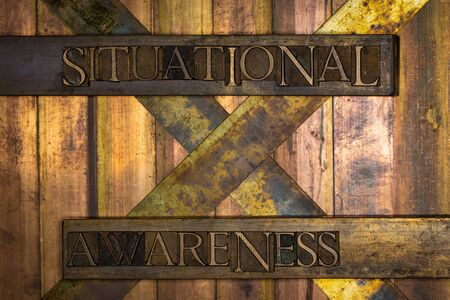 Photo of real authentic typeset letters Situational Awareness text on vintage textured grunge copper and gold background