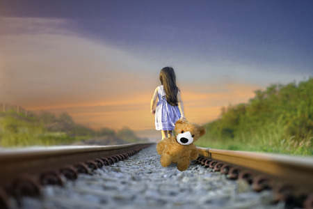 a little girl run away home on the railway, walking lonely ahead without destination