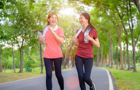 Photo pour young asian women doing exercise running in city public park - image libre de droit