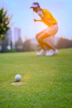 Photo pour young woman golf player mostly success to putting golf ball into the hole on the green of the golf course, cheerfully of woman golf player in background - image libre de droit