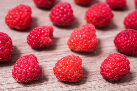 Red ripe raspberry lie on a wooden background. Copyspace, flat lay, top view. Macro