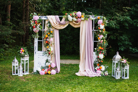 Foto de Beautiful wedding ceremony outdoors. Wedding arch made of cloth and white and pink flowers on a green natural background. Old doors, rustic style. - Imagen libre de derechos