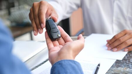 Photo pour Business concept, car insurance, sell and buy car, car financing, car key for Vehicle Sales Agreement. New carowners are taking keys from male salespeople. - image libre de droit