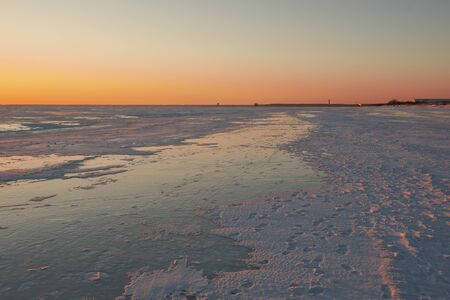 View to the frozen beach of Baltic sea and pier of PÀrnu on horizon in the light of sunset on sunny and cold winter evening, Estonia
