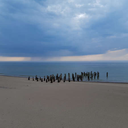 Photo pour Abandoned and collapsed wooden pier on the sandy Baltic sea shore.  Stormy clouds over the sea - image libre de droit