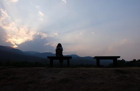 Silhouette of young woman watching warm setting sun.