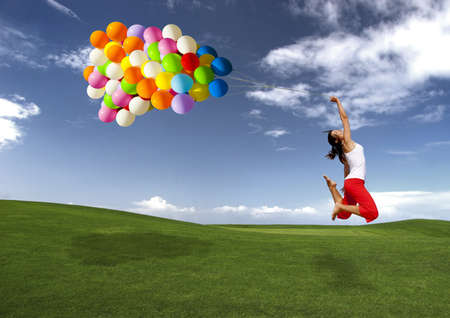 Beautiful and athletic Girl jumping with balloons on a green meadow