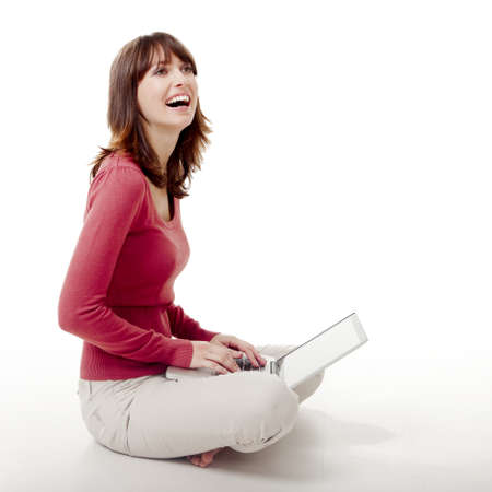 Beautiful woman sitting on the floor laughing  and working with a laptop