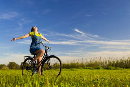 Happy girl over a bicycle and looking the view, in a green meadow