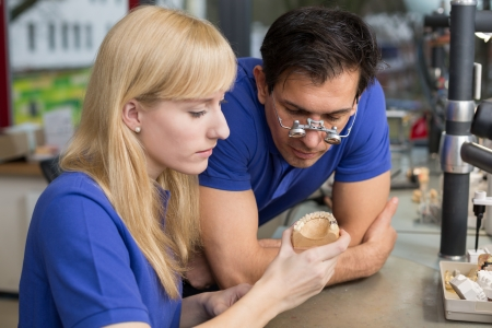 Dental technician or apprentice showing a prosthesis to a collegue or instructor