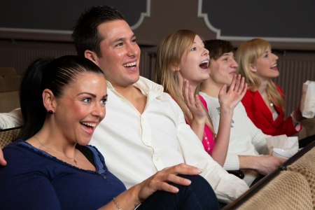 Laughing people in a cinema or theatre watching a movie or a play