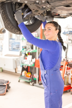 Woman repairing the brakes of a car on hydraulic lift