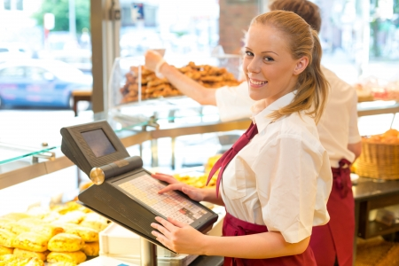 Cashier in a bakery posing with cash register