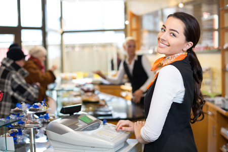Saleswoman working at cash register or checkout counter in shop