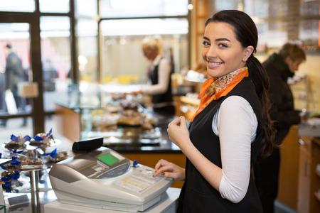 Saleswoman working at cash register in shop