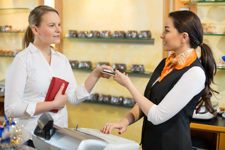 Client at shop paying at cash register with saleswoman