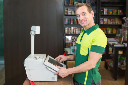 Cashier at cash register in shop or store with books in background