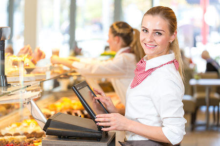 Shopkeeper or saleswoman at bakery working at cash register