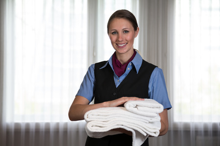 Maid in a hotel posing with towels in bedroom