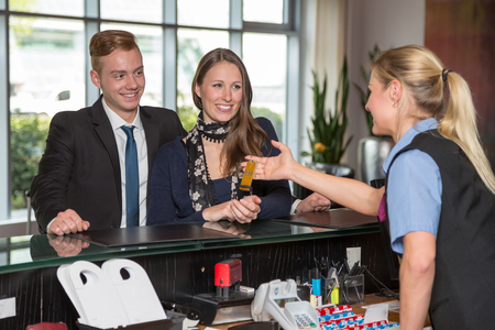 Hotel receptionist handing over key to two customers