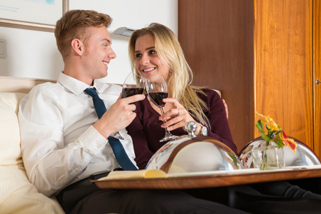 Couple with tray of wine and food in a hotel room