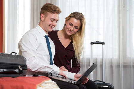 Couple in Hotel room looking at laptop computer