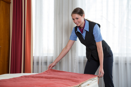Maid or room service making the bed in a hotel room