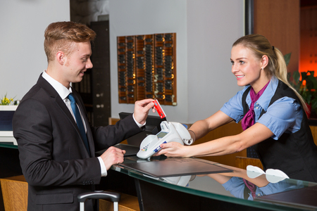 Guest in a hotel paying with credit card at reception