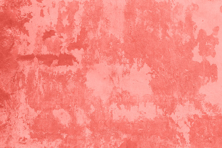 Photo pour Stone wall with cracked, peeling plaster and paint as texture, background, coral toned. - image libre de droit