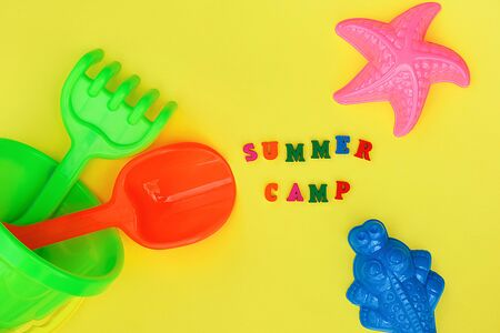 Text Summer camp and multicolored set children\'s toys for summer games in sandbox or on sandy beach on yellow background. Creative top view Flat lay Concept children\'s rest and development.