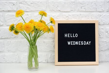 Photo for Hello Wednesday words on black letter board and bouquet of yellow dandelions flowers on table against white brick wall. Concept Happy Monday. Template for postcard. - Royalty Free Image