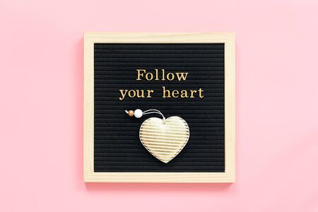 Photo pour Follow your heart. Motivational quote in gold letters and decorative textile heart on black letter board on pink background. Top view Flat lay Concept inspirational quote of the day. - image libre de droit