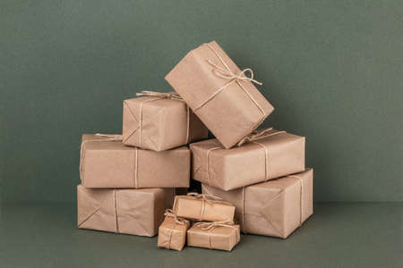 Foto für Lots of gifts boxes in craft paper with twine on green background. Holiday concept. Front view. - Lizenzfreies Bild