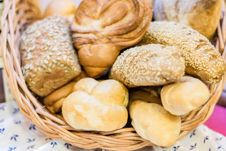 Photo pour close up of freshly baked wheat bread with sesame and shugar in wicker basket - image libre de droit