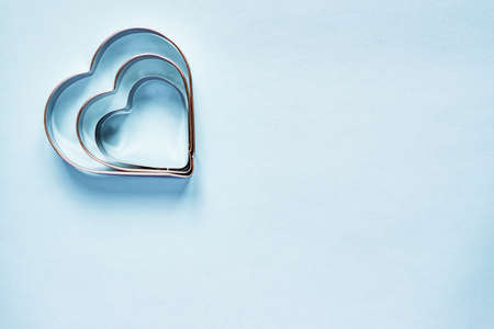Photo pour Three metal cookie cutters in heart shape on light blue background with copy space - image libre de droit