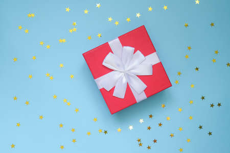 Photo for red gift box with white bow on color blue background with star shaped confetti. Festive greeting card. Holiday concept - Royalty Free Image