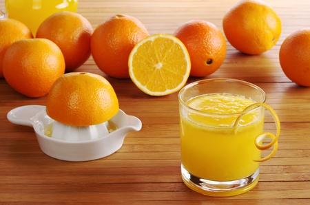Fresh orange juice with orange juice squeezer and oranges on wooden mat (Selective Focus)