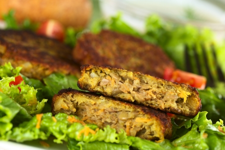 Vegetarian lentil burger made of brown lentils and grated carrots served on lettuce (Selective Focus, Focus on the upper half burger)