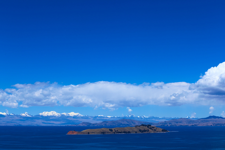 The Isla de la Luna (Island of the Moon) with the snow-capped mountains of the Andes in the back photographed from the Isla del Sol (Island of the Sun) in Lake Titicaca, Bolivia. The islands are a popular travel destination.