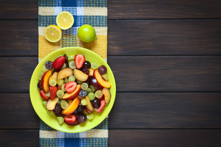 Overhead shot of fresh fruit salad made of grape, strawberry, plum and nectarine served on plate with lemon above, photographed on dark wood with natural light