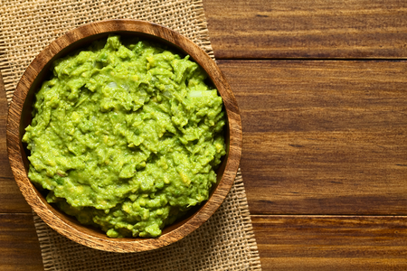 Avocado dip or guacamole in wooden bowl, photographed overhead with natural light (Selective Focus, Focus on the avocado dip)