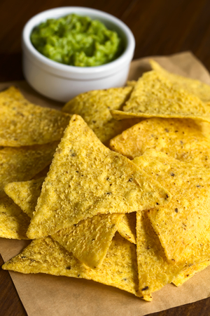 Corn tortilla chips with avocado dip in the back, photographed with natural light (Selective Focus, Focus one third into the image)