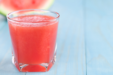 Photo pour Refreshing watermelon juice on blue wood, copy space on the right side (Selective Focus, Focus on the front of the glass rim) - image libre de droit
