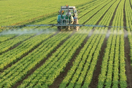 farming tractor spraying a field