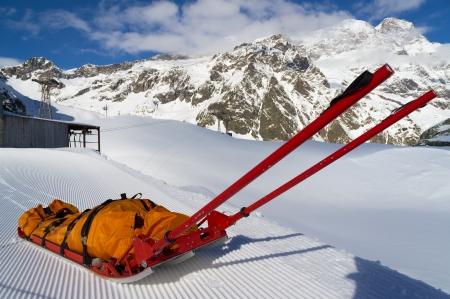 Empty mountain rescue sled over snow on mountain