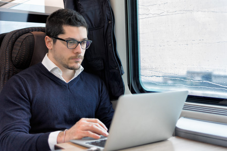 young man working on laptop computer on the train