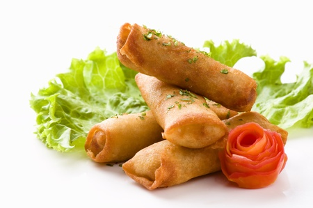 A horizontal image of four egg rolls sprinkled with parsley served on a white ceramic plate with a leaf of lettuce and a flower shaped tomato