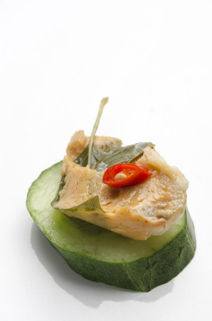 A vertical image of a spicy Thai fish and basil p?t? and cucumber canap? toped with a slice of red pepper served on a white ceramic plate
