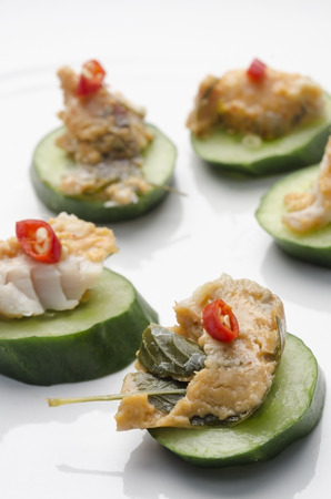A vertical image of a spicy Thai fish and basil pate and cucumber canap?s toped with a slice of red pepper served on a white ceramic plate