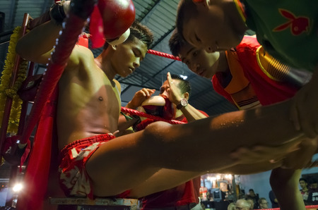 Hua Hin, Thailand - January 8, 2016: A Muay Thai boxer rests between two rounds as he receives instructions from his trainer at the boxing stadium in Hua Hin, Thailand on January 8, 2016. Muay Thai boxing is considered by many as the national sport of Tha